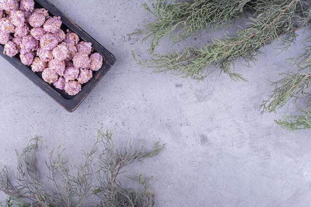 Groenblijvende takken naast een dienblad met snoep gecoate popcorn op marmeren achtergrond. hoge kwaliteit foto