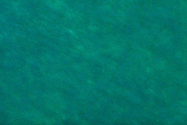 Groene achtergrond van vilten stof. textuur van wollen textiel