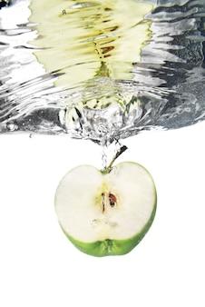 Groene appel daalde in water met bellen die op wit worden geïsoleerd