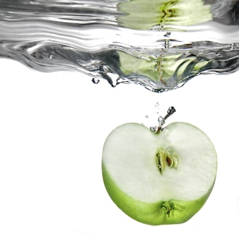 Groene appel in het water gevallen met splash geïsoleerd op wit