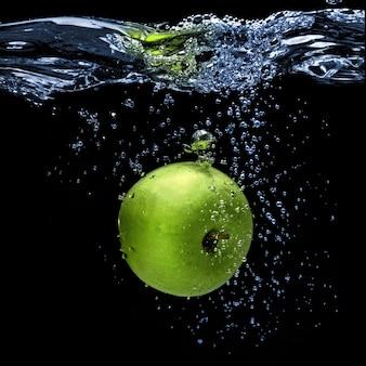Groene appel in het water gevallen met splash geïsoleerd op zwart