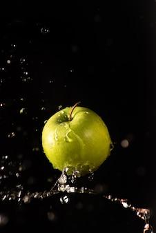 Groene appel met mooie scheut water met zwarte achtergrond en selectieve aandacht.