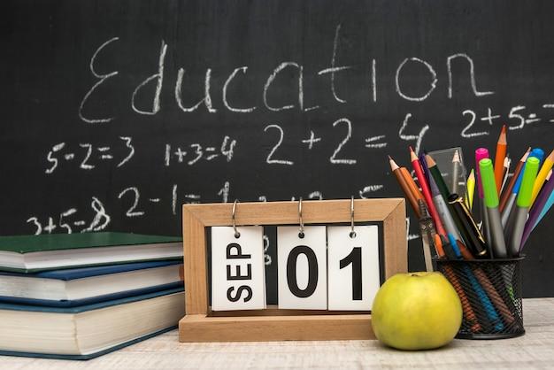 Groene appel met stapel boeken en het schrijven van leveringen tegen bord. onderwijs concept