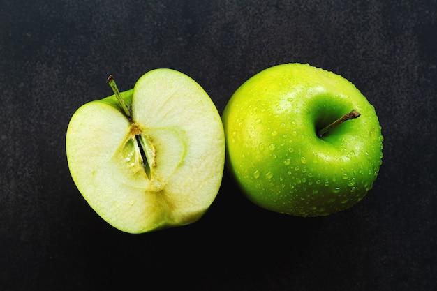 Groene appel op een donkere ondergrond met waterdruppels