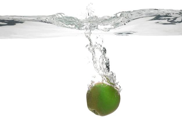 Groene appel valt in het water. nuttig vitaminevoedsel