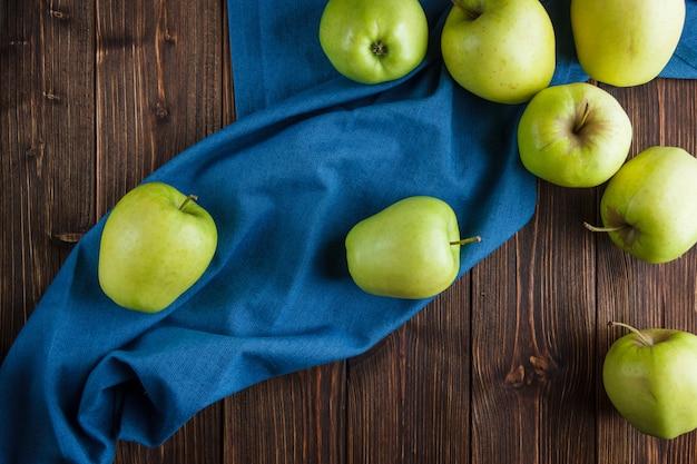 Groene appels bovenaanzicht op een blauwe doek en houten achtergrond