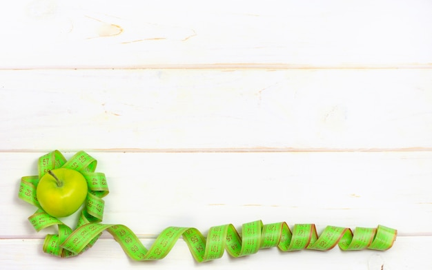 Groene appels en centimeter voor metingen op een witte achtergrond.