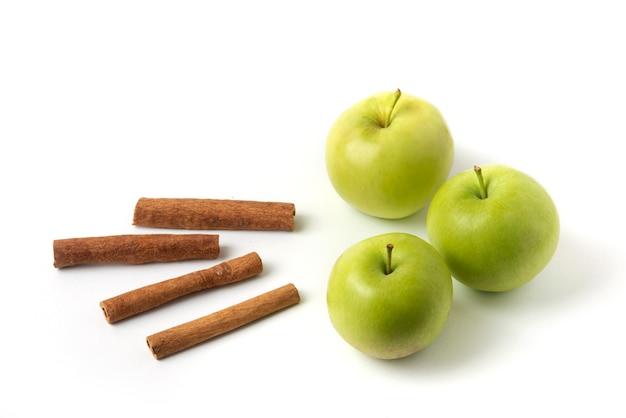 Groene appels en kaneel op wit wordt geïsoleerd