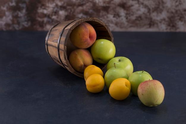Groene appels en sinaasappelen uit een houten emmer op marmer.