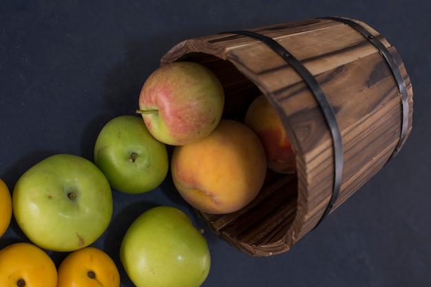 Groene appels en sinaasappelen uit een houten emmer op zwart.