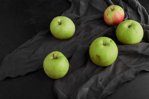 Groene appels geïsoleerd op zwart oppervlak op grijs tafelkleed, bovenaanzicht.