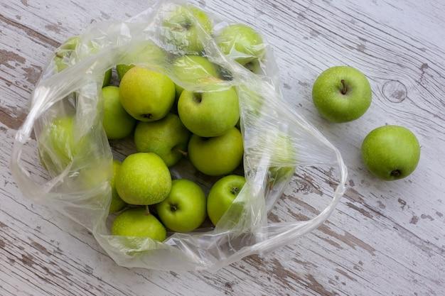 Groene appels in een pakket op een houten tafel
