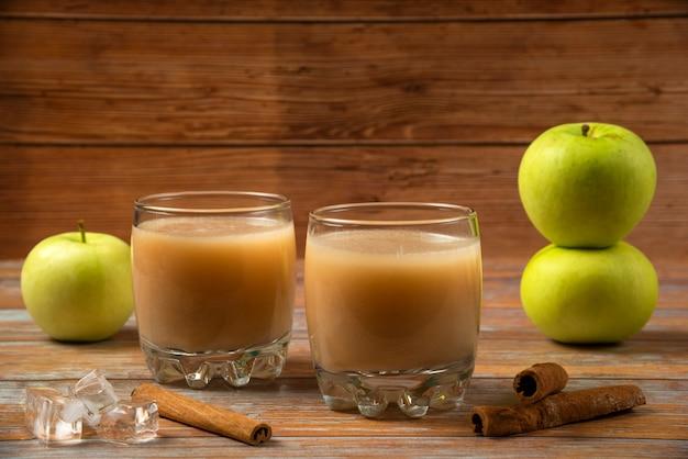 Groene appels, kaneelstokjes en twee kopjes vers sap op tafel