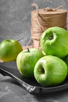 Groene appels liggend op een grijs met een zwarte plaat ecologische verpakking.