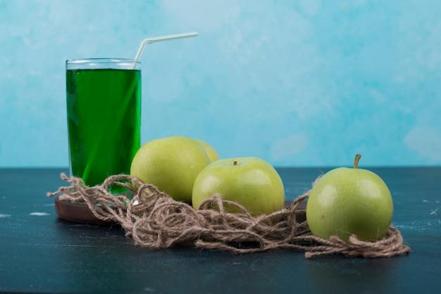 Groene appels met een glas sap op een houten bord.