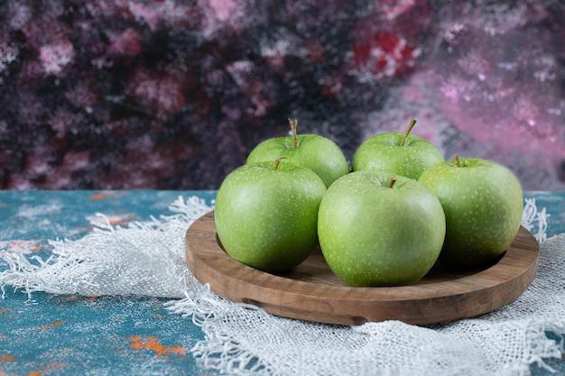 Groene appels op houten schotel op blauw.