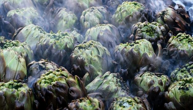Groene artisjokken bakken op de hete kolen in de vuurpot op de markt voor verkoop van dichtbij. gezond voedselconcept.