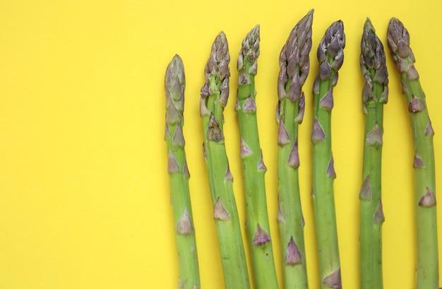 Groene asperges op een felgele tafel. lente seizoensgroenten.