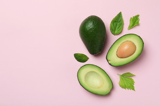 Groene avocado en bladeren op roze