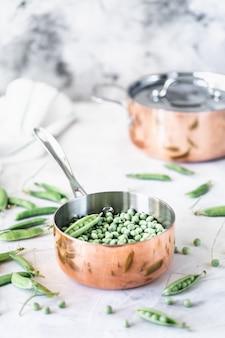 Groene babyerwten in pan op wit