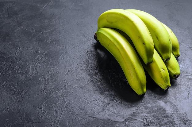 Groene bananen. zwarte achtergrond. bovenaanzicht ruimte voor tekst