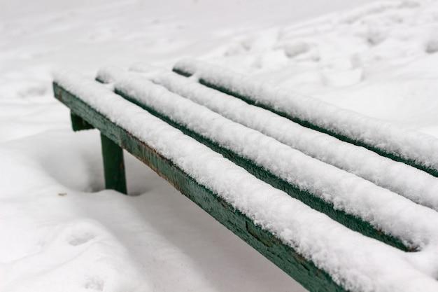 Groene bank bedekt met sneeuw