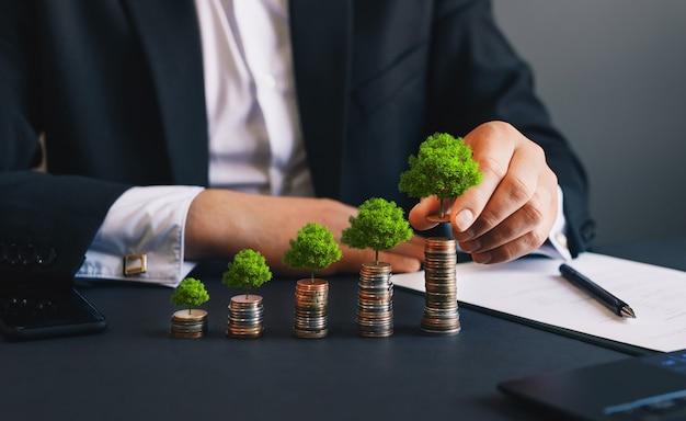 Groene bedrijfsgroei zakenman die munt houdt met boom die op de stapel van geldmuntstukken groeit