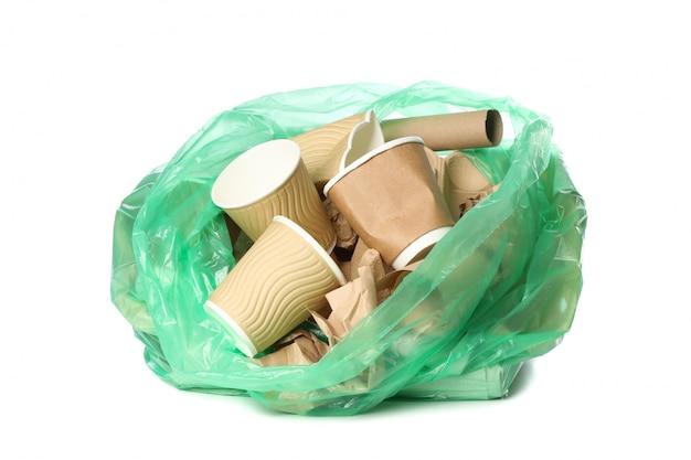 Groene beschikbare zak met verschillend die afval op witte achtergrond wordt geïsoleerd