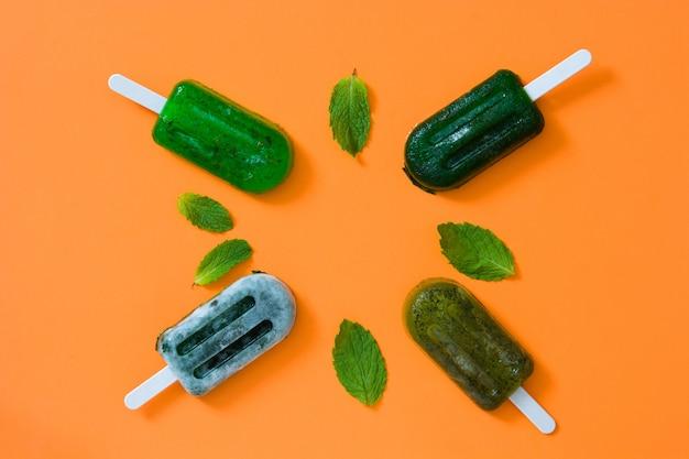 Groene bevroren ijslollys op de oranje mening van de lijstbovenkant