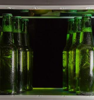 Groene bierflesjes op de plank in de koelkast. de mist op het glas.