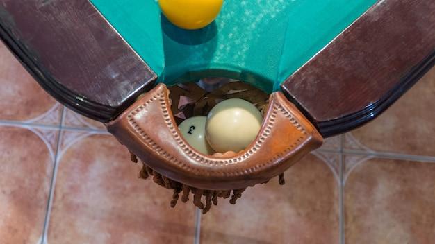 Groene biljarttafel met witte ballen. bal bij het gat. detailopname. bovenaanzicht