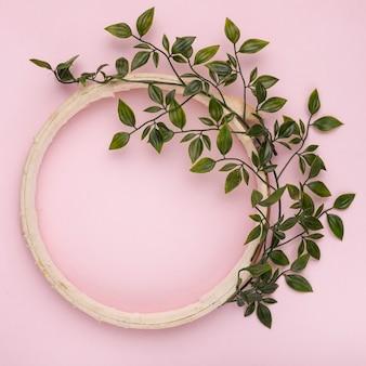 Groene bladeren die op houten leeg cirkelkader tegen roze achtergrond worden verfraaid