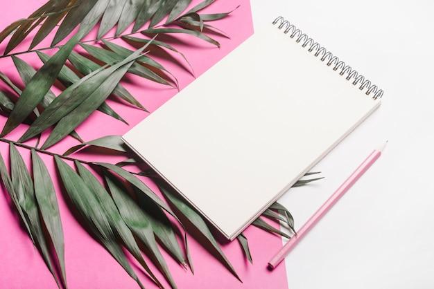Groene bladeren; lege spiraalvormige blocnote en roze potlood op dubbele achtergrond
