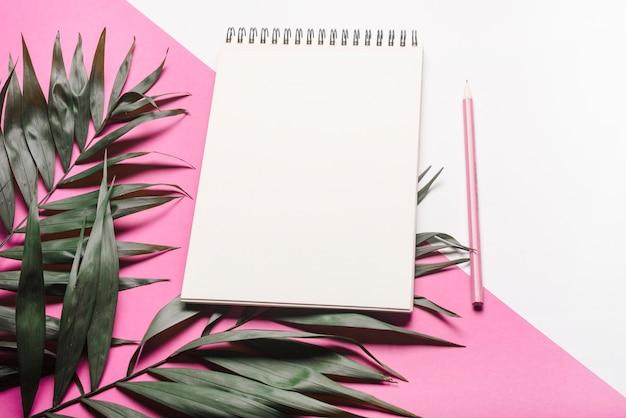 Groene bladeren met lege spiraalvormige blocnote en roze potlood op dubbele achtergrond