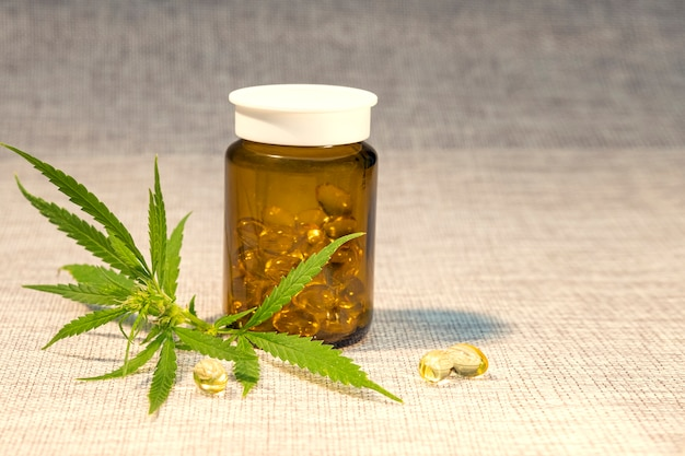 Groene bladeren van medicinale cannabis en olie-extract in een potje met capsules.