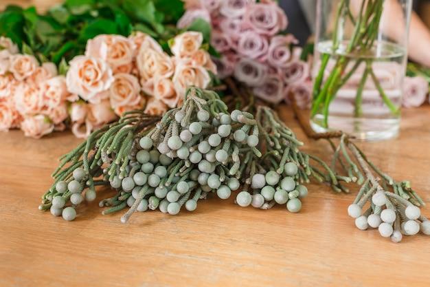 Groene bloemen en verse rozen voor bezorging van een boeket. floral design studio, het maken van decoraties en arrangementen.