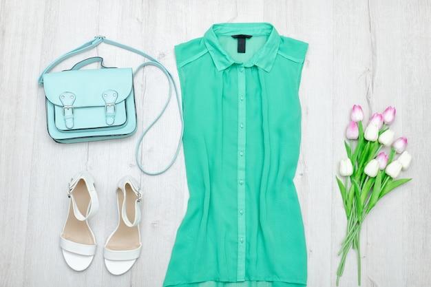 Groene blouse, witte schoenen, munttasje en een boeket tulpen. modieus concept. houten achtergrond
