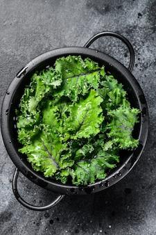 Groene boerenkoolsalade in een vergiet. biologische vegetarische gerechten. zwarte achtergrond. bovenaanzicht.