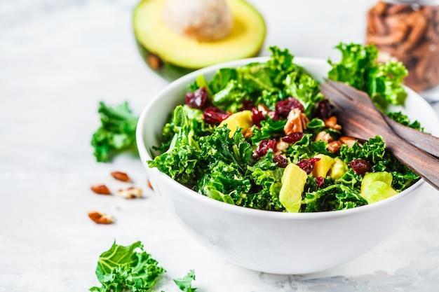 Groene boerenkoolsalade met amerikaanse veenbessen en avocado in witte kom. gezond veganistisch voedselconcept.