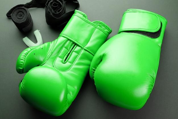 Groene bokshandschoenen en verbanden op een donkere achtergrond