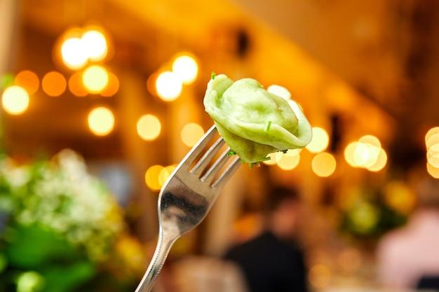 Groene bollen op een vork op kleurenachtergrond