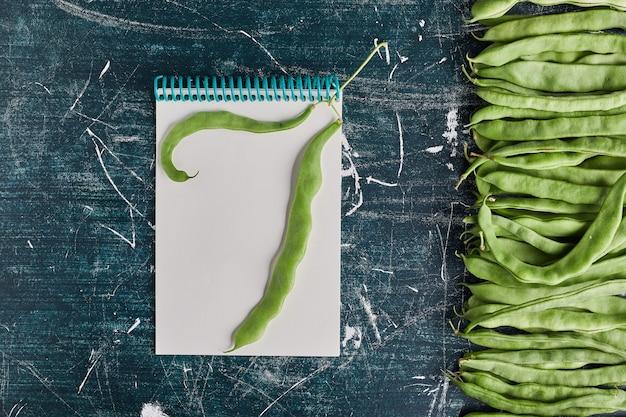 Groene bonen op een stuk blanco papier.