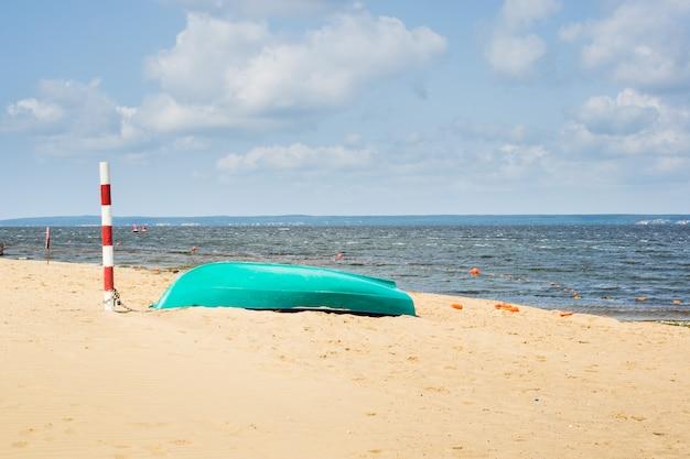Groene boot vastgebonden aan een rode en witte pilaar op een zandstrand en boeien in een rivier