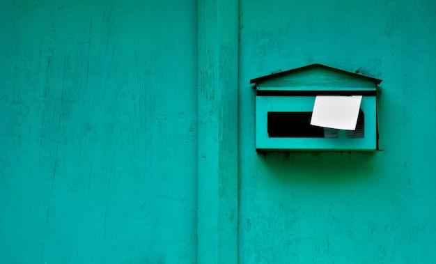 Groene brievenbus bij oude houten deur