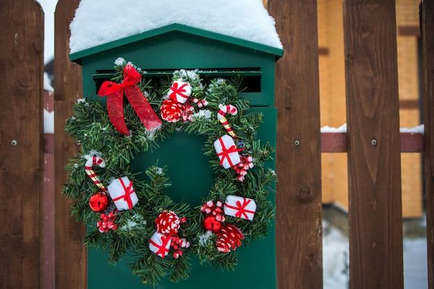 Groene brievenbus met kerstmiskroon op een houten omheining. interieurdecoratie.