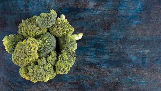 Groene broccoli verspreid op blauwe tafel