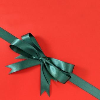 Groene cadeau lint boog hoek diagonale rode papier achtergrond