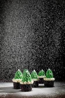 Groene cakes met de toevoeging van witte room in de vorm van kerstbomen worden in verschillende volgorde bestrooid met poedersuiker