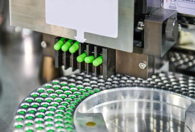 Groene capsule geneeskunde pil productielijn, industrieel farmaceutisch concept.