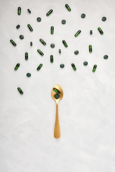 Groene capsules verspreid over en op een gouden lepel op een lichte achtergrond